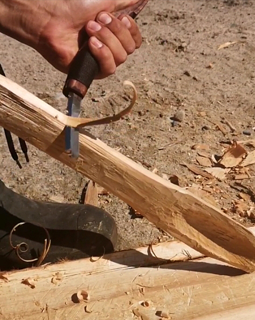 hand holding knife and scraping wood stick