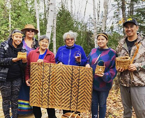 Group of Indigenous young people and elders holding hand woven baskets and mats outside