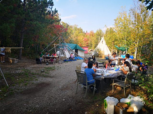 group of people of various ages eating together outside on tables with teepee in background