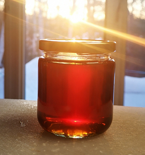 jar of honey in front of window with sunlight coming through it